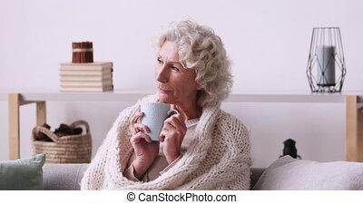 Peaceful 60s senior grandmother in warm plaid enjoying ...