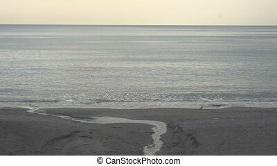 peaceful and calm shot of a gently lapping sea and nice sky.
