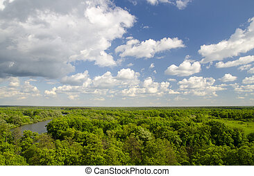 Peaceful atmosphere of white clouds, river and green forest