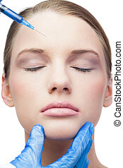 Peaceful attractive model on white background having botox injection on the forehead