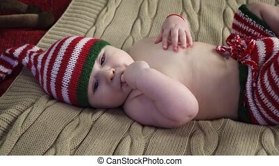 Peaceful baby boy dressed in striped cap and pants is lying on bed, sucking a finger and smiling