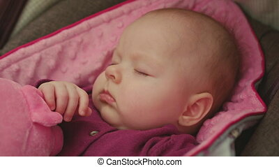 Peaceful Baby Sleeping in a Car Seat on pink blanket holding pink toy