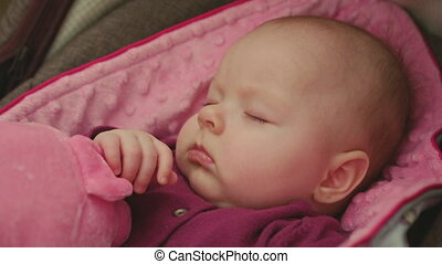 Peaceful Baby Sleeping in a Car Seat on pink blanket with pink toy