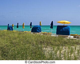 Peaceful Beach Cabanas - A row of beach cabanas with yellow...