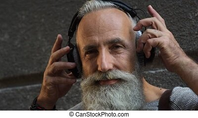 Peaceful bearded man taking off headphones in street
