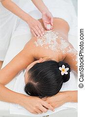 Peaceful brunette getting a salt scrub beauty treatment in...