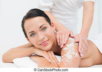 Peaceful brunette getting a salt scrub beauty treatment