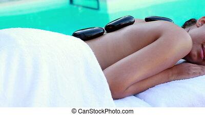 Peaceful brunette getting hot stone massage