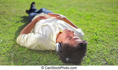 Peaceful brunette man lying on the grass while listening to music