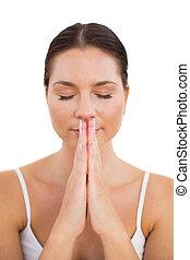 Peaceful brunette meditating with hands together
