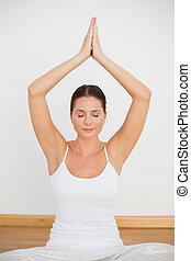 Peaceful brunette sitting and meditating in lotus pose