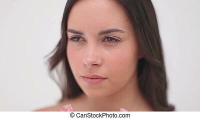 Peaceful brunette woman massaging her cheeks