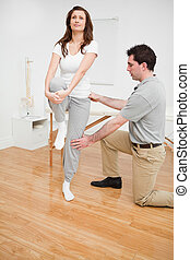 Peaceful brunette woman stretching her leg in a room