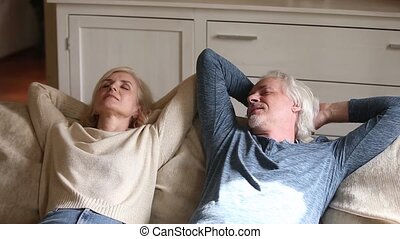 Peaceful calm senior couple relaxing on soft comfortable...