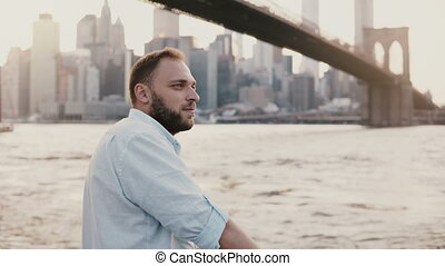 Peaceful Caucasian young man comes up and stands at river embankment near New York City scenery, enjoying the view 4K.