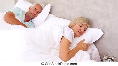 Peaceful couple sleeping in bed at home in bedroom