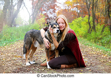 Peaceful Happy Woman Hugging German Shepherd Dog While Walking in Autumn Woods