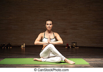 Peaceful lady putting hands to her chest and meditating