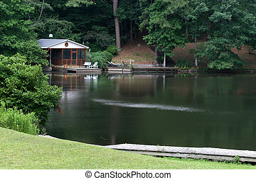 A quiet serene peaceful lake with a cabin and a dock