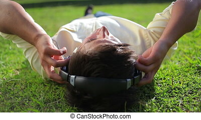 Peaceful man listening to music while lying on the grass in...