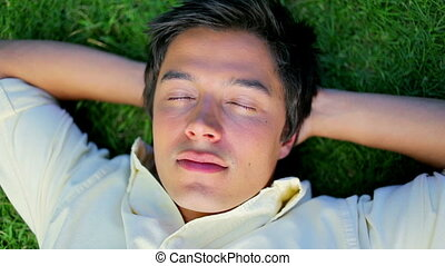 Peaceful man napping while lying on the grass