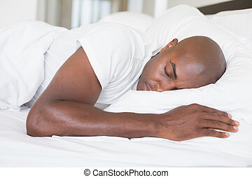 Peaceful man sleeping in bed at home in the bedroom