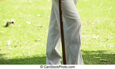 Peaceful man standing while using a cane in the countryside