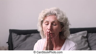 Peaceful middle aged 60s woman praying God for good luck. - ...
