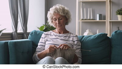 Peaceful middle aged retired hoary woman knitting woolen scarf.