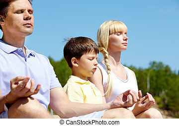 Peaceful minute - Photo of three family members meditating...