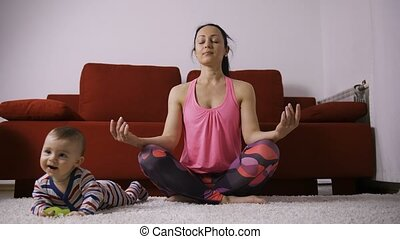 Peaceful mother meditating in lotus pose near baby