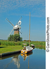 A tranquil scene of a boat and windmill so typical of the Norfolk Broads, England