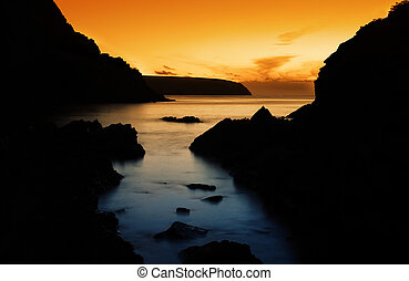 Peaceful Ocean Sunset - Rocky Silhouette with beautiful...