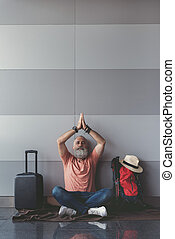 Peaceful old man relaxing in waiting hall