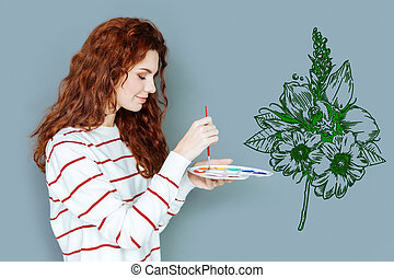 Peaceful painter holding a color palette while drawing