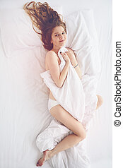 peaceful portrait of happy young woman in bed