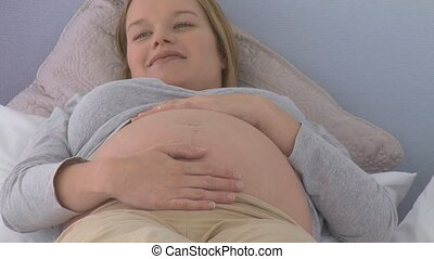Peaceful pregnant woman on her bed