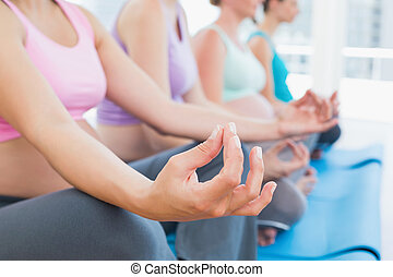 Peaceful pregnant women meditating in yoga class in a...