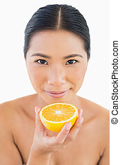 Peaceful pretty woman holding orange slice in her hand