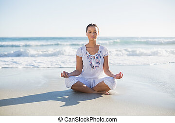 Peaceful pretty woman in lotus position on the beach on a...