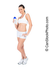 Peaceful pretty woman in sportswear holding flask