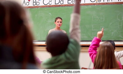 Peaceful pupils raising their arms n the classroom