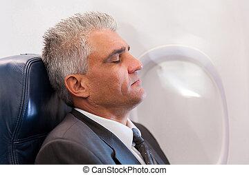 senior businessman resting on airplane
