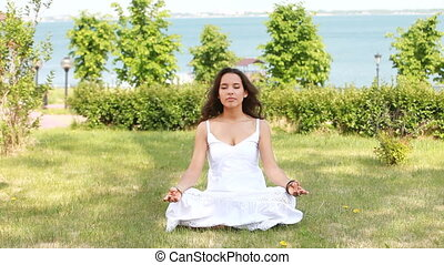 Peaceful - Adorable young woman sitting in lotus pose and...