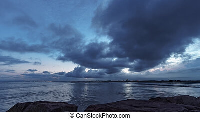 Peaceful sunset with ocean and city lights from breakwater -...