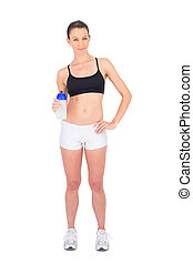 Peaceful woman in sportswear holding flask