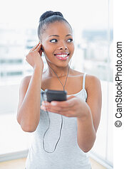 Peaceful woman in sportswear listening to music
