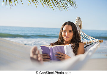 Peaceful woman lying on hammock reading book