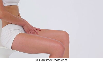 Peaceful woman massaging her legs