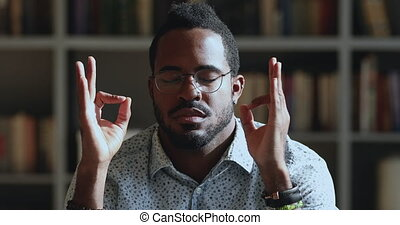 Peaceful young african ethnicity man reducing stress at work...